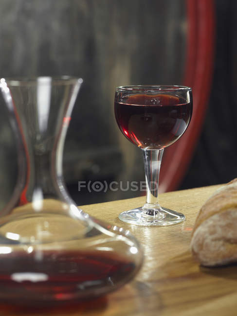 Still life of glass of red wine and decanter by loaf of bread — Stock Photo