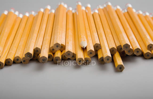 Pile of unsharpened pencils with one sharpened pencil amid — Stock Photo