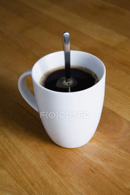 White mug of black coffee with spoon on table — Stock Photo