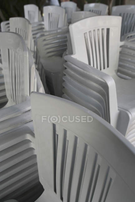 Stock Sedie In Plastica.Full Frame Shot Of Stacked White Plastic Chairs Close Up Large