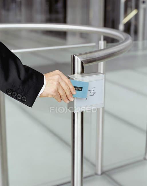 Buisnessman в руки, проведіть ідентифікації біля воріт безпеки — стокове фото