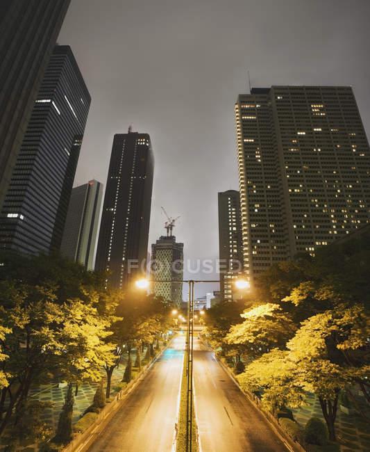 Via vuota in mezzo a grattacieli di notte — Foto stock