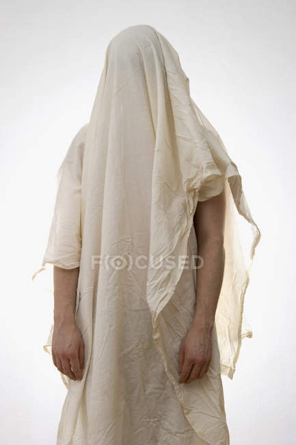 Person standing underneath white sheet — Stock Photo