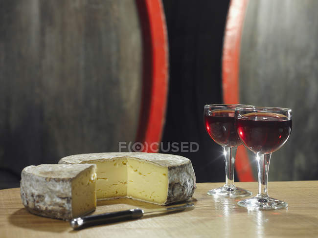 Still life of glasses of red wine and wheel of cheese on background of barrels in winery cellar — Stock Photo