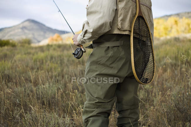 Midsection of man holding fly rod at country — Stock Photo