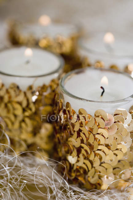 Close up view of lit candles decorated with sequins — Stock Photo