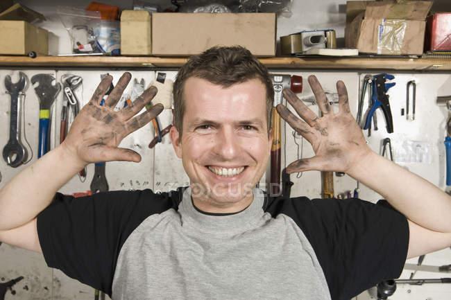 Портрет усміхнений чоловік тримає брудних рук — стокове фото