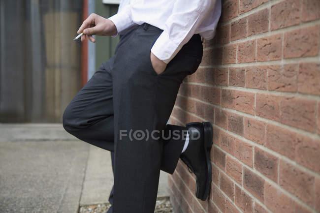 Parte baixa de um homem de negócios que se inclina contra uma parede e fuma um cigarro — Fotografia de Stock