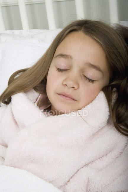 Uma menina dormindo na cama dentro de casa — Fotografia de Stock