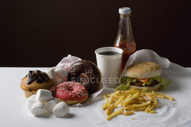 Still life of American fast food meal and snack food on black background — Stock Photo
