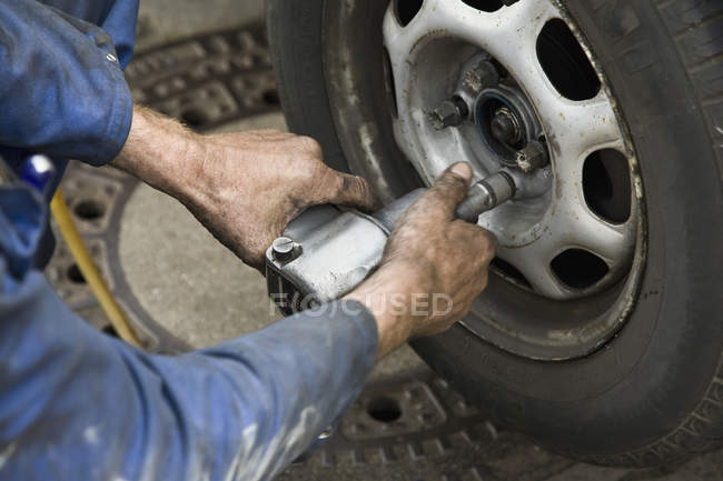 Car mechanic's hands unscrewing wheel with pneumatic screwdriver — Stock Photo