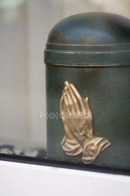 Urna de cremação colheita com rezando baixo-relevo as mãos — Fotografia de Stock