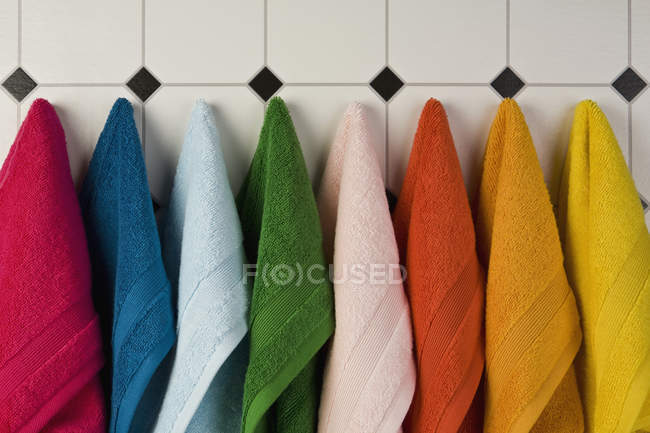 Multi colored towels hanging in row on tiled wall — Stock Photo