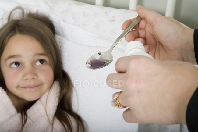 A mother giving unwell daughter medicine — Stock Photo