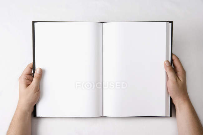 Crop male hands holding open book with blank pages — Stock Photo
