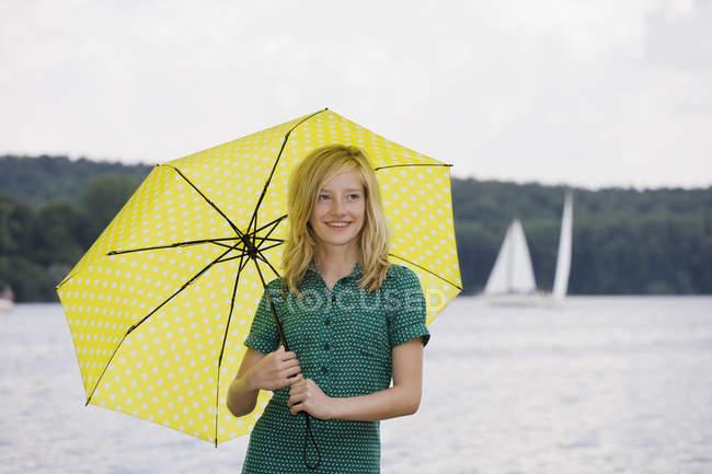 Retrato de niña de pie en el lago bajo el paraguas en nublado — Stock Photo