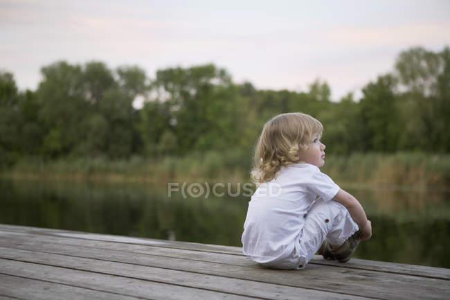 Un garçon assis sur une jetée — Photo de stock