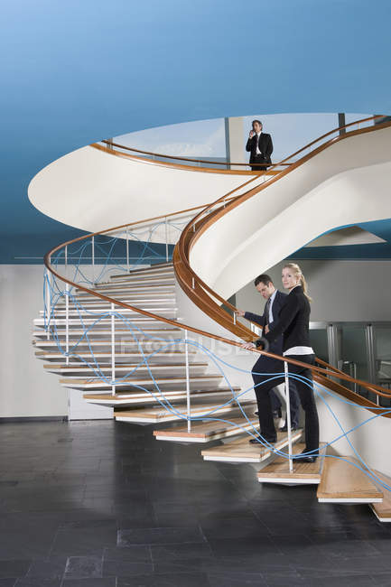 Business people walking up a staircase — Stock Photo