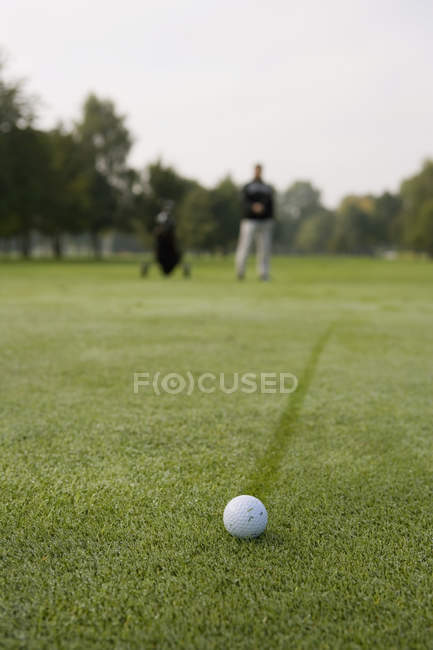Balle de golf contre personne floue sur le putting green — Photo de stock