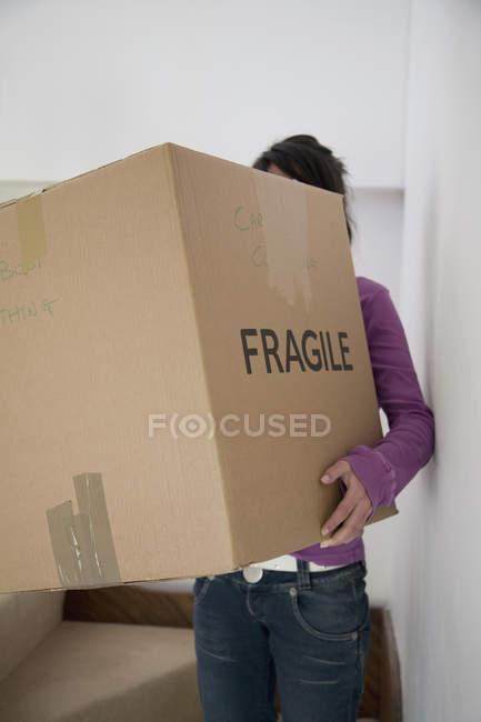 Femme portant une boîte en carton — Photo de stock