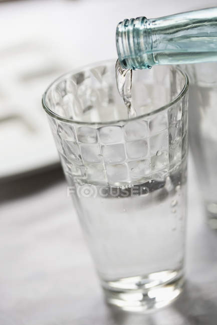 Bottled water pouring into glass — Stock Photo