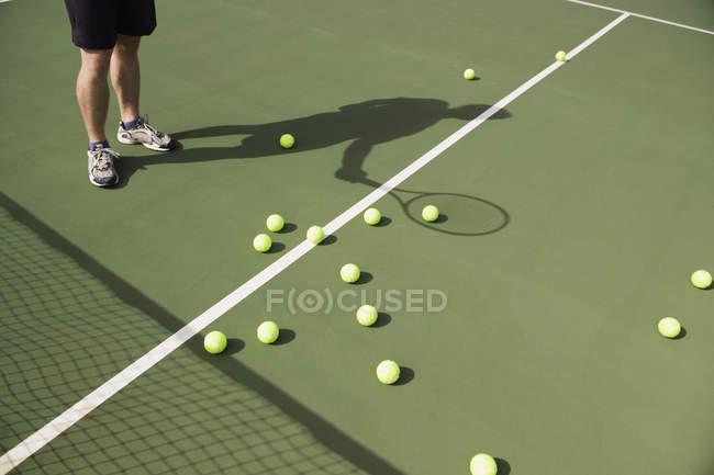 Sección baja de un jugador de tenis con bolas en corte - foto de stock