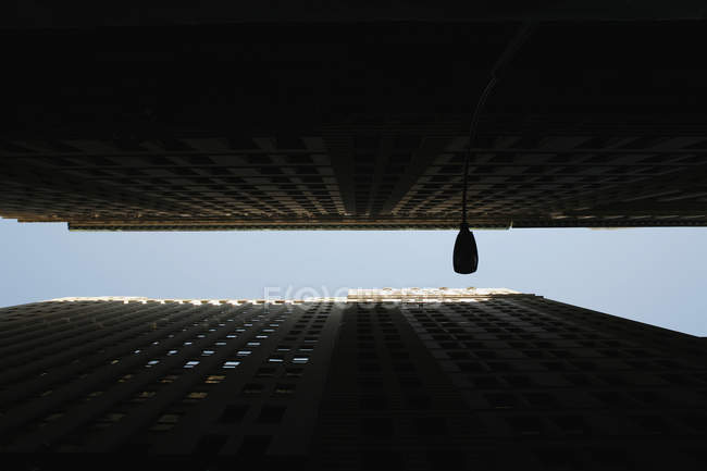 Bottom view of two tall buildings facade in shadow — Stock Photo