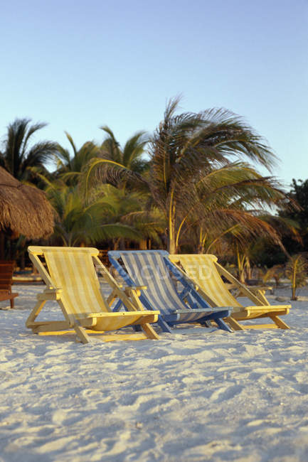 Tree empty sun loungers on tropical beach — Stock Photo