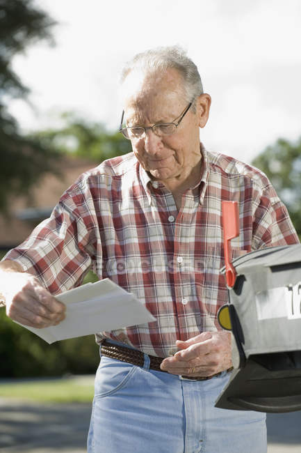 A senior man checking the mailbox — Stock Photo