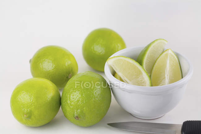 Limes and bowl of lime wedges with knife on white background — Stock Photo