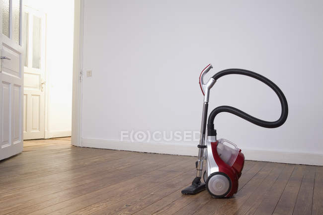 Vacuum cleaner amid of empty room — Stock Photo