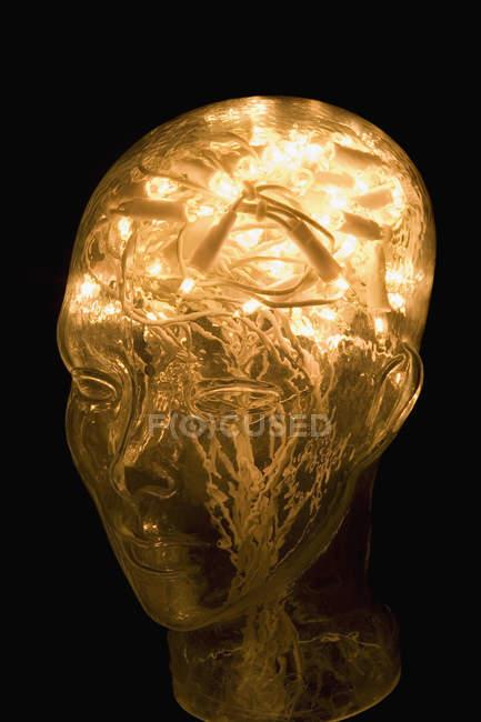 Cabeza de vidrio llena de hilo de luces de hadas sobre negro - foto de stock