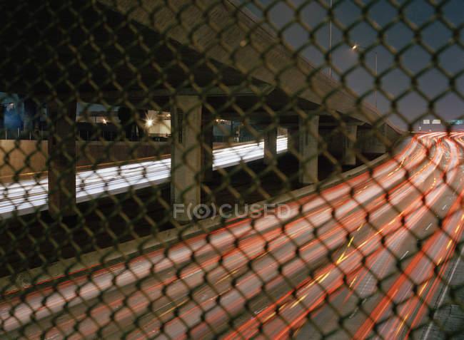 Tir longue exposition de la circulation autoroutière, visible à travers la clôture de la grille — Photo de stock
