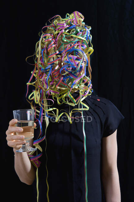 Woman with streamers covering face holding glass of champagne — Stock Photo