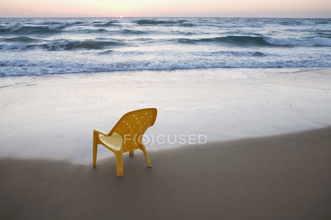 Empty plastic chair on sand beach with surfing waves — Stock Photo