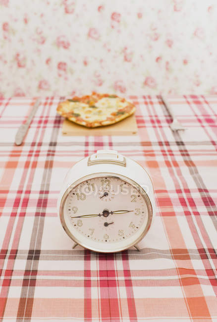 Old fashioned clock on table with a pizza — Stock Photo