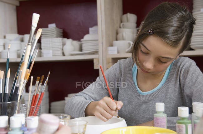 A young girl painting a bowl in a pottery studio — Stock Photo