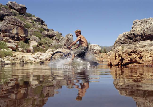 Um homem montado em uma bicicleta de montanha, através de um fluxo — Fotografia de Stock