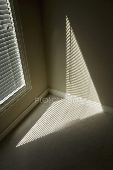 Shatters sunlight pattern on wall and floor of room — Stock Photo