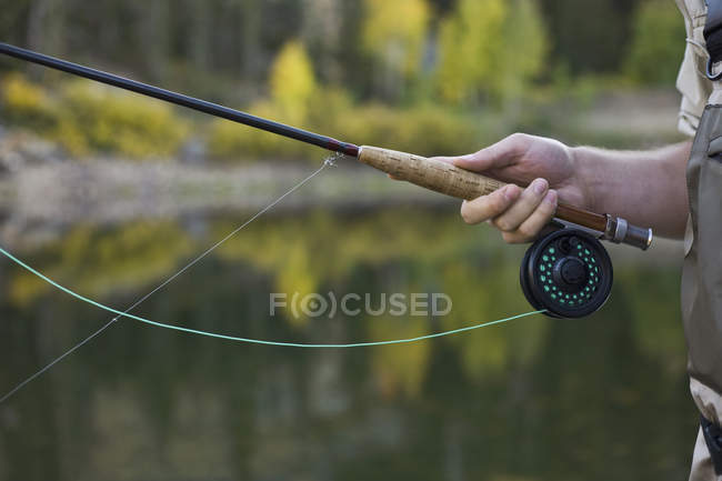 Crop male hand holding fly rod — Stock Photo