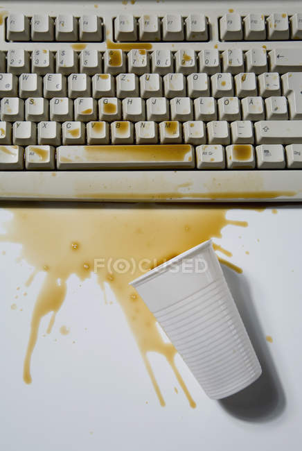 Spilled coffee cup with paddle on computer keyboard — Stock Photo