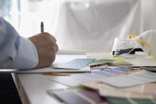 Обтинання чоловічого рукописний текст почерк в блокноті столом з зразки кольорів — стокове фото