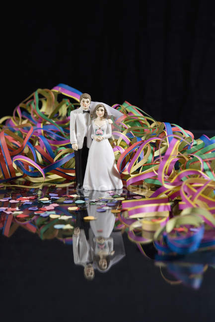 Розтяжки і конфетті оточують фігурки нареченого і нареченої — стокове фото