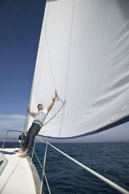 Человек, прислонившийся к парусу яхты в море — стоковое фото