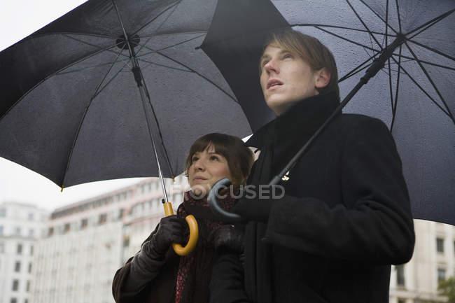 Jeune couple tenant des parasols — Photo de stock