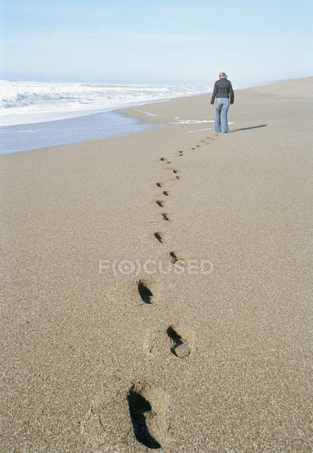 Rear view of woman walking along sand beach — Stock Photo
