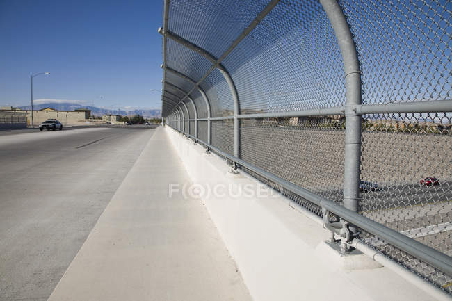Bending fence at highway overpass on sunny day — Stock Photo