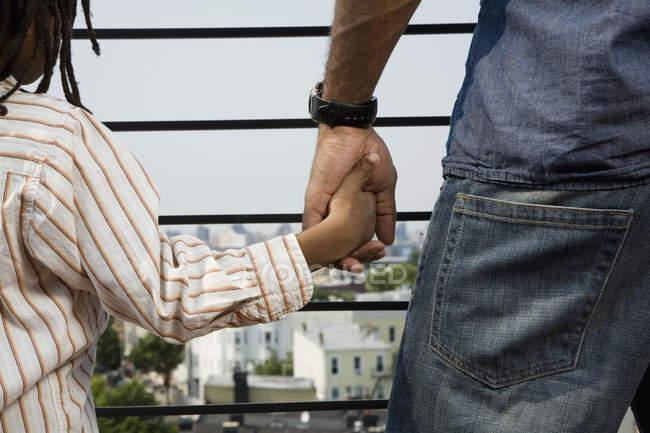 Abgeschnittenes Bild von Vater und Sohn beim Händchenhalten auf Balkon — Stockfoto