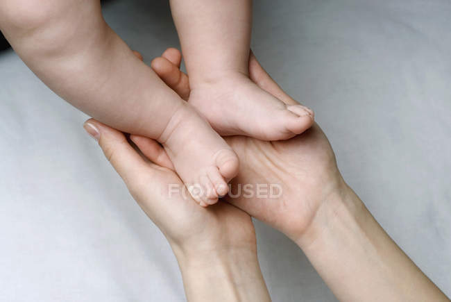 Crop female holding newborn baby's feet — Stock Photo