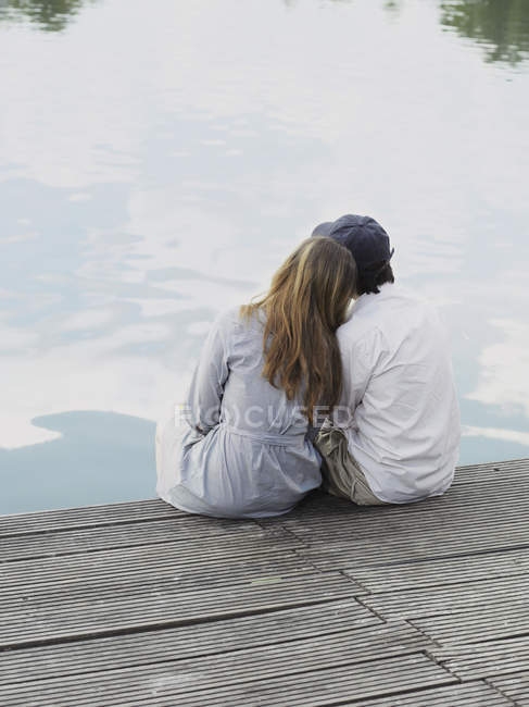 Rear view of young couple sitting on jetty — Stock Photo